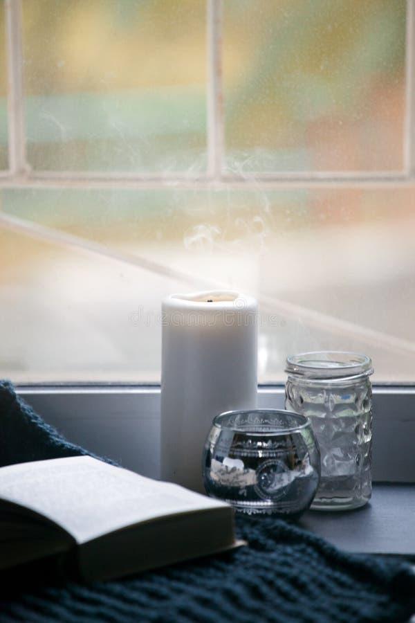Todavía la vida con los detalles interiores y las velas ardientes en la sala de estar, el concepto de comodidad casera e interior imagen de archivo libre de regalías