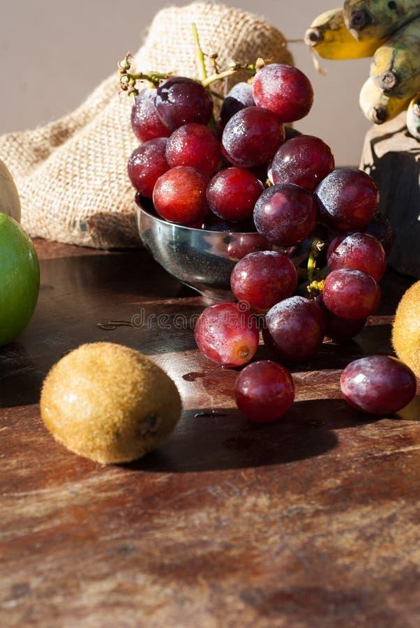 Todavía la vida da fruto con la pera china, el kiwi, la manzana roja, las uvas y el Cu fotografía de archivo