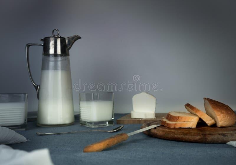 Todavía vida 1 Cena rústica jarro de leche, velas, té, huevos, pan, rollos, queso, en la tabla imágenes de archivo libres de regalías