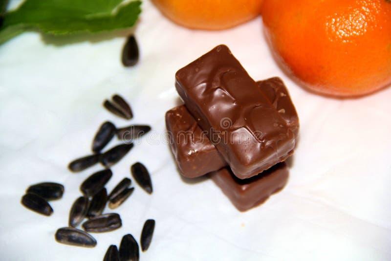 Todavía vida: Chocolates, semillas y mandarinas fotos de archivo libres de regalías