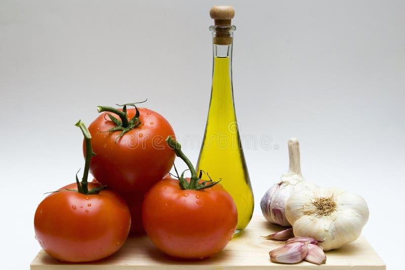 Todavía vida con ajo, petróleo y tomates imagen de archivo