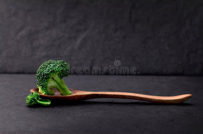 Todavía vida con bróculi verde fresco en la placa de piedra negra fotos de archivo