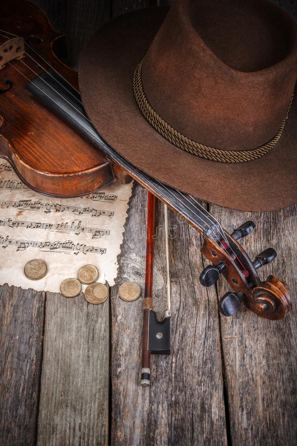 Todavía vida con el sombrero, el violín y las monedas foto de archivo