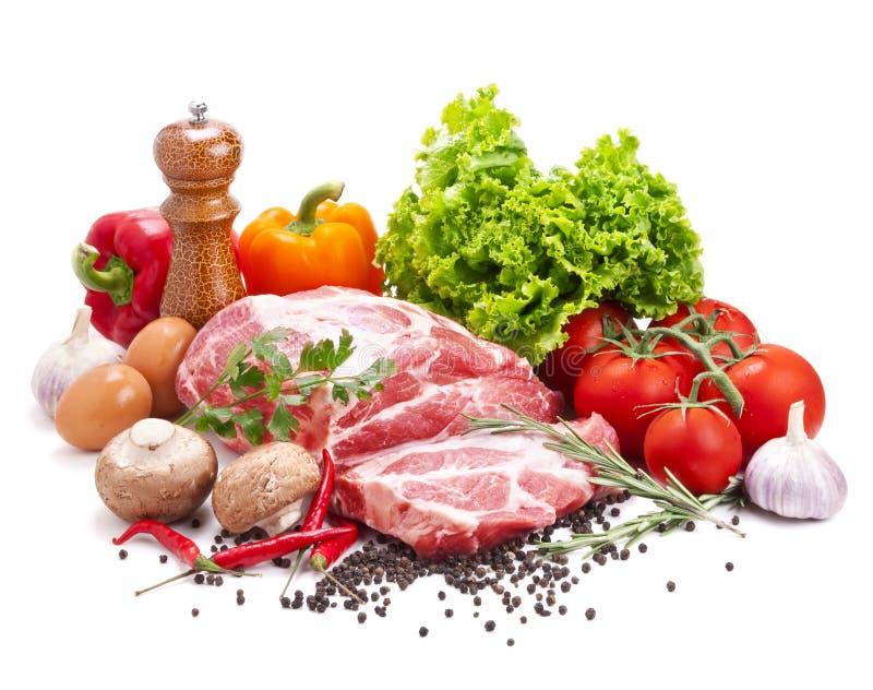 Todavía vida con la carne de cerdo sin procesar y las verduras frescas fotos de archivo libres de regalías