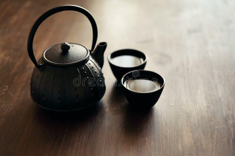 Todavía vida con la tetera y las tazas de té del este tradicionales en el escritorio de madera fotos de archivo