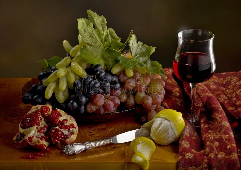 Todavía vida con la uva, el limón, la granada y el vino imágenes de archivo libres de regalías
