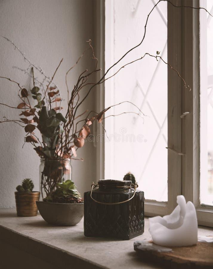 Todavía vida con la ventana y una vela y un florero foto de archivo