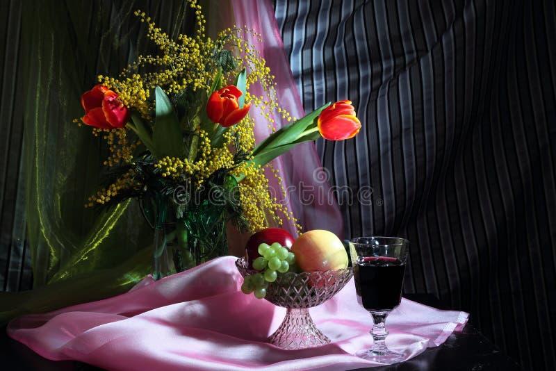 Todavía vida con las flores, el vino rojo y las frutas imágenes de archivo libres de regalías