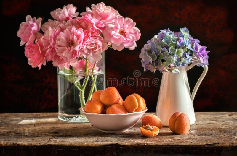 Todavía vida con las flores y los albaricoques fotos de archivo