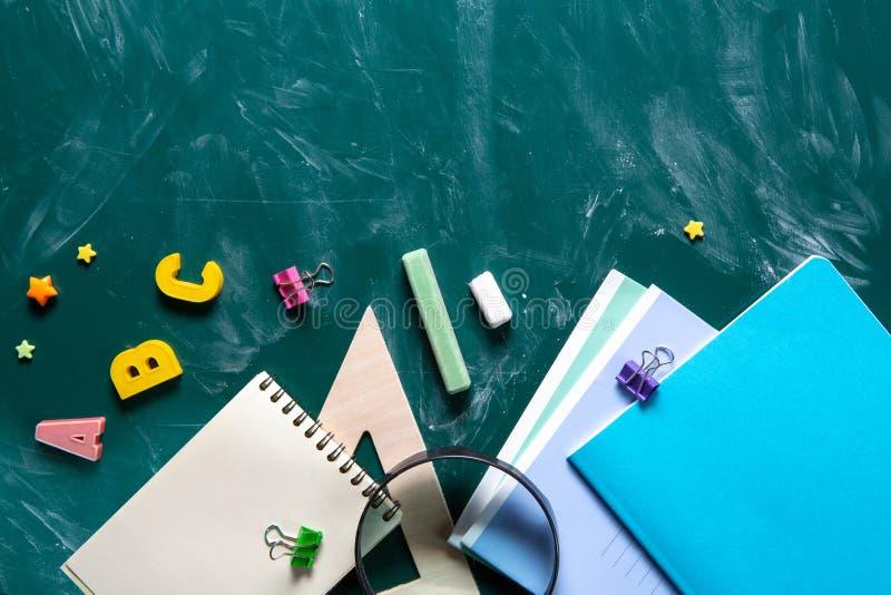 Todavía vida con las fuentes de escuela Pizarra en pizarra de la tiza Fondo verde Cuadernos, cuadernos, rotuladores, coloreados fotos de archivo libres de regalías