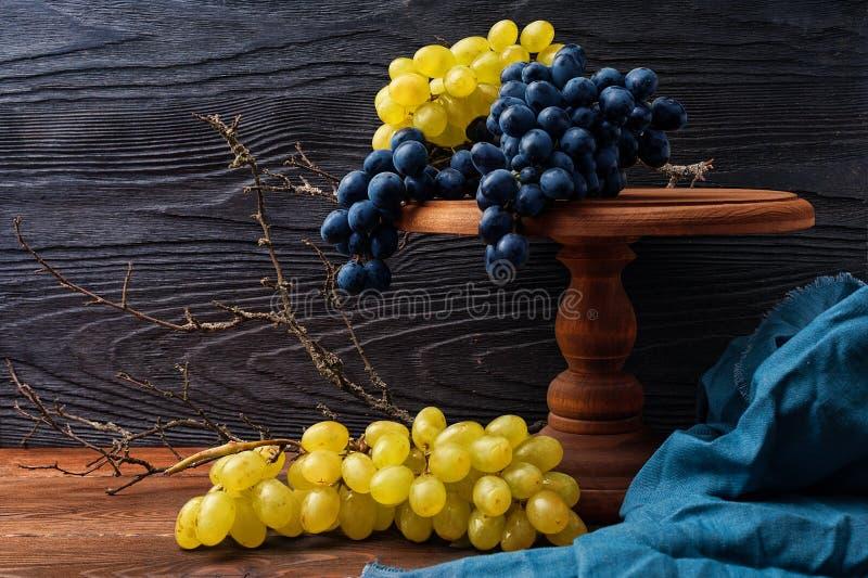 Todavía vida con las uvas azules y verdes fotografía de archivo