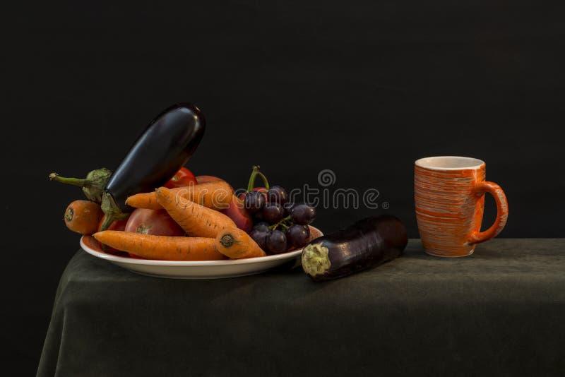 Todavía vida con las verduras en una placa y una taza anaranjada imágenes de archivo libres de regalías