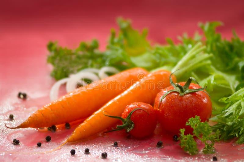 Todavía vida con las verduras lavadas - zanahorias, tomates imagenes de archivo