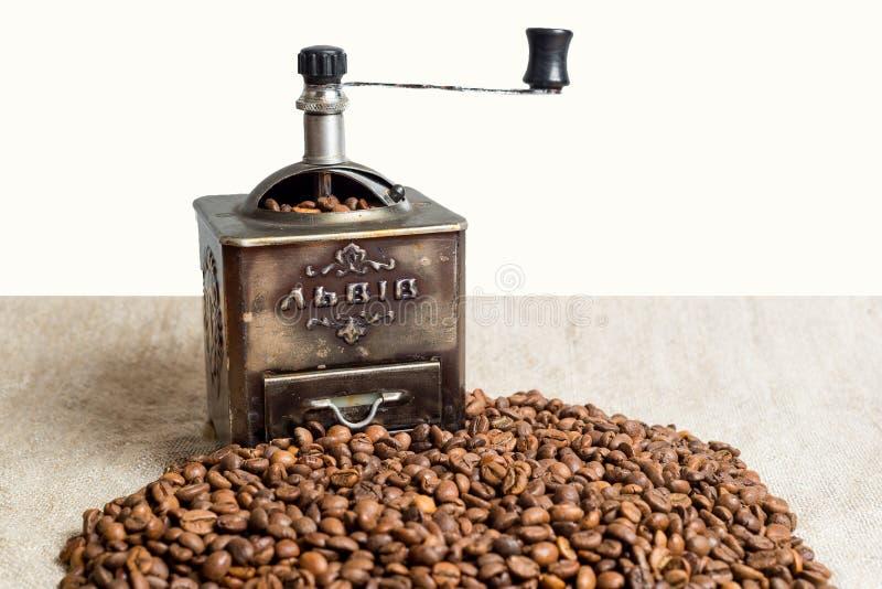 Todavía vida con los granos de café y el molino de café viejo en el fondo de madera imagenes de archivo