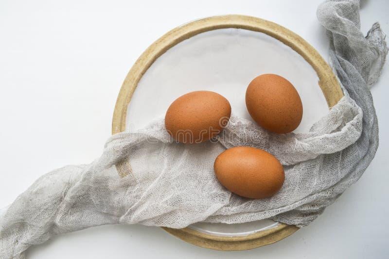 Todavía vida con los huevos crudos frescos en la placa en el fondo blanco Copie el espacio fotografía de archivo