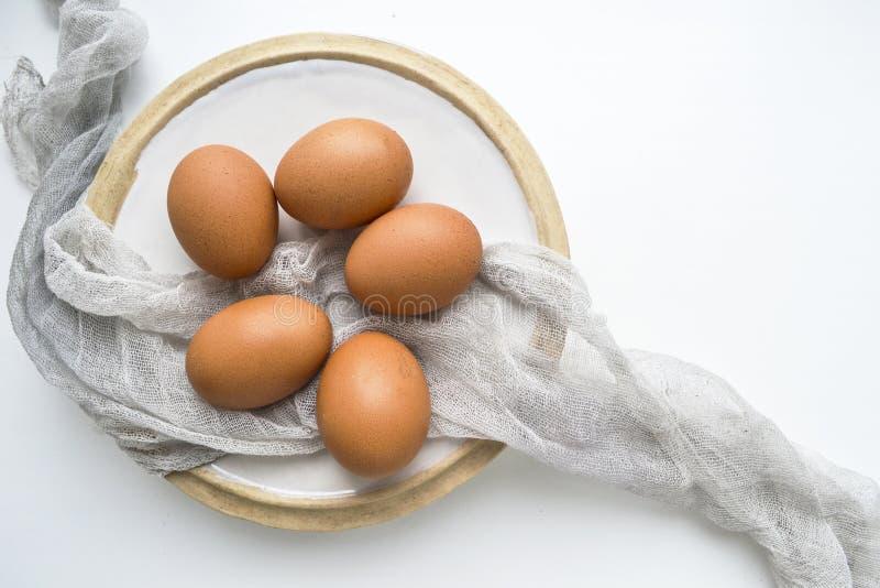 Todavía vida con los huevos crudos frescos en la placa en el fondo blanco Copie el espacio foto de archivo libre de regalías