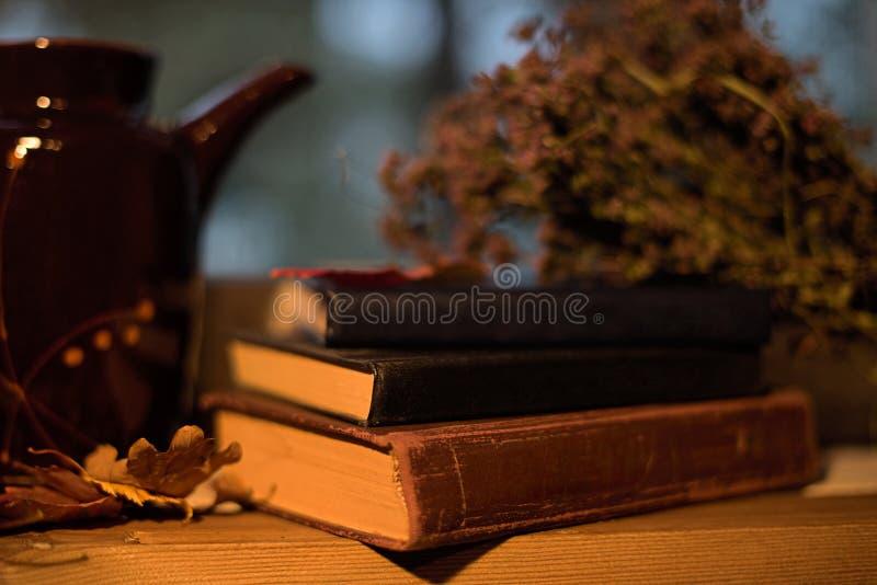 Todavía vida con los libros, té, tetera, hierbas en el alféizar imágenes de archivo libres de regalías