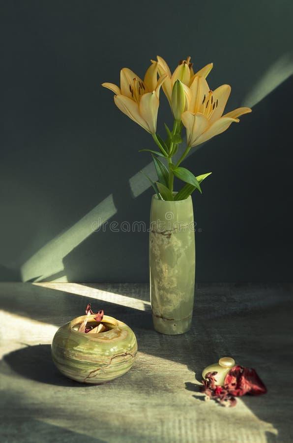 Todavía vida con los lirios en un florero verde hecho de piedra natural fotografía de archivo