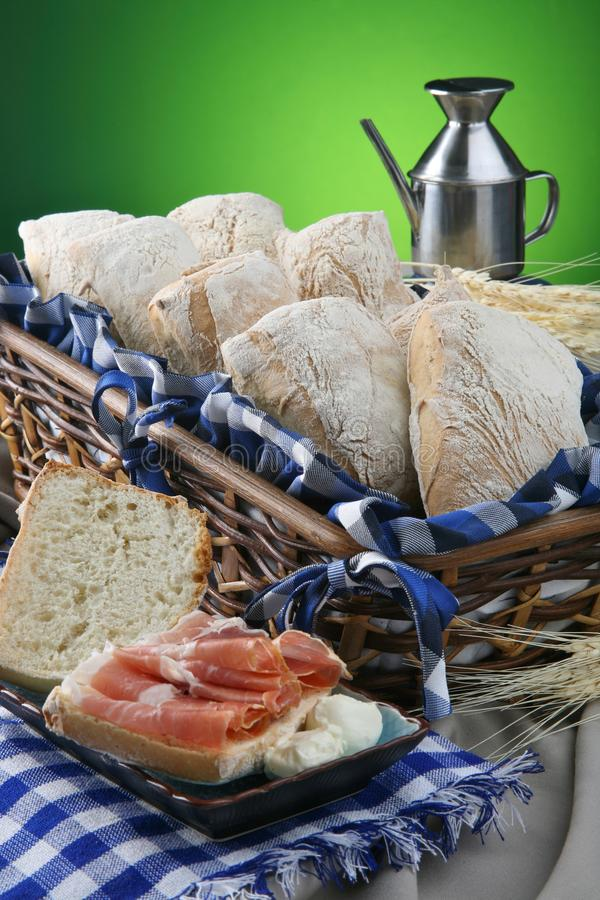 Todavía vida con panes, el jamón de Serrano y el aceite de oliva Pan de Ciabatta foto de archivo
