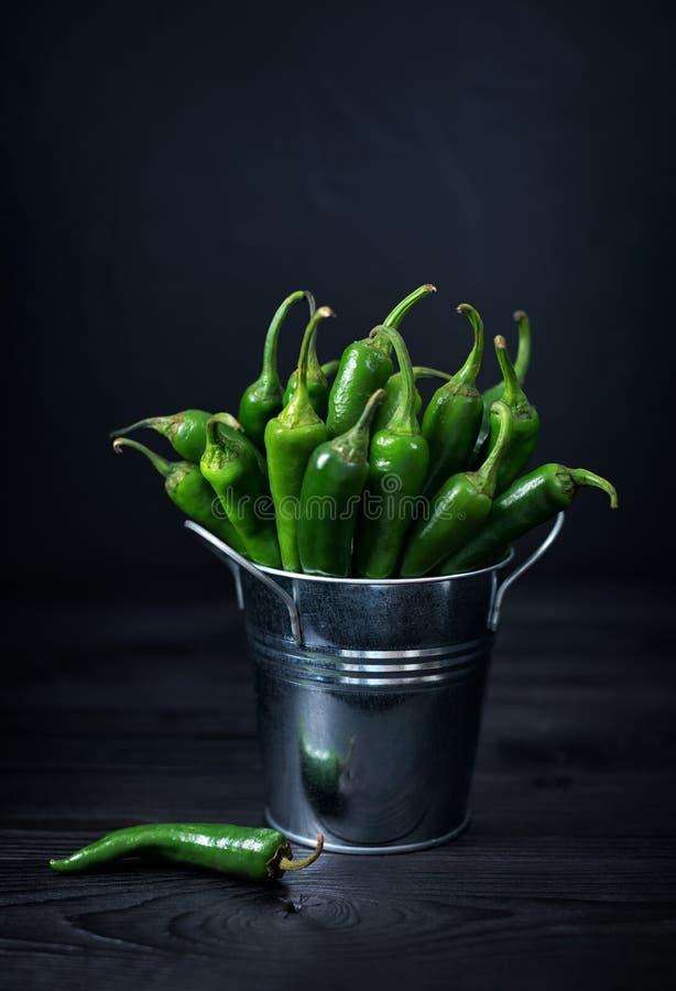 Todavía vida con pimienta de chiles verde en la tabla de madera fotografía de archivo libre de regalías