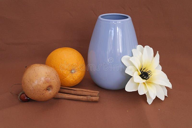 Todavía vida con un florero, una fruta y una flor azules foto de archivo