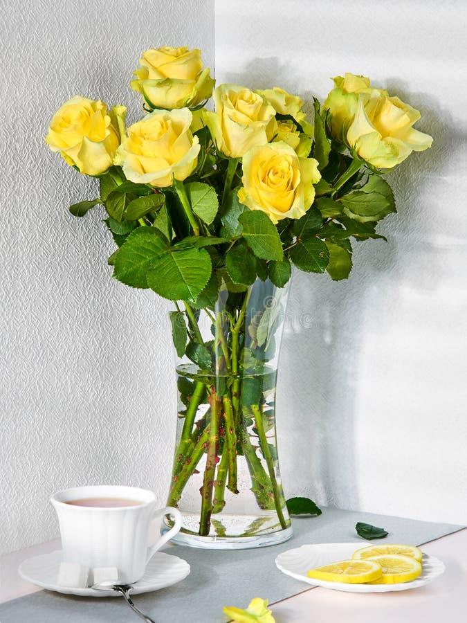 Todavía vida con un ramo de rosas amarillas y de una taza de té foto de archivo
