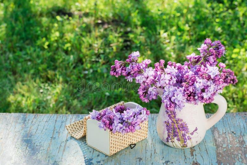 Todavía vida con una lila en un jarro, un ataúd en una tabla de madera fotos de archivo libres de regalías