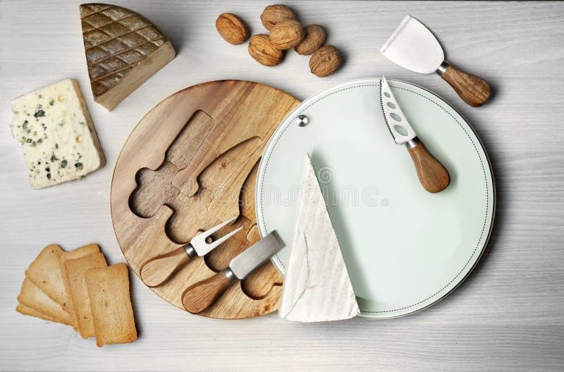 Todavía vida con una mesa redonda para cortar los quesos y las diversas herramientas que cortan fotos de archivo libres de regalías