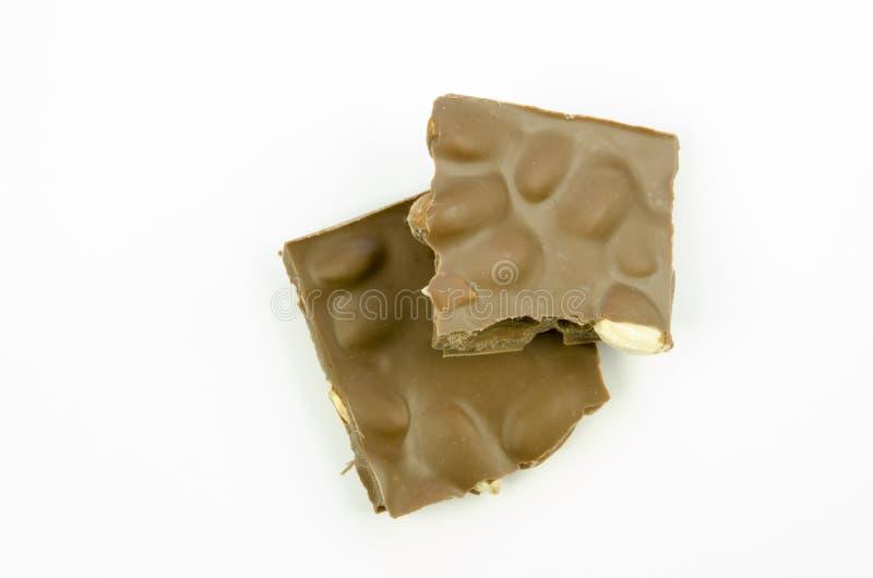 Todavía vida con una opinión del primer de una tabla quebrada de chocolate con leche con las almendras aisladas imagenes de archivo
