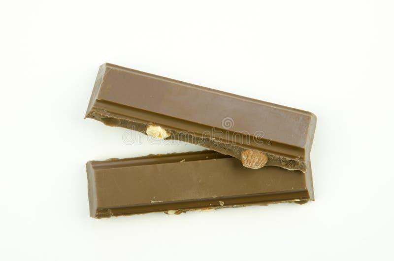 Todavía vida con una opinión del primer de una tabla quebrada de chocolate con leche con las almendras aisladas imagen de archivo libre de regalías