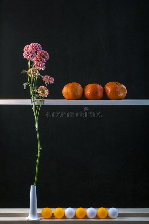 Todavía vida con una rama, las mandarinas y las bolas de la flor fotografía de archivo