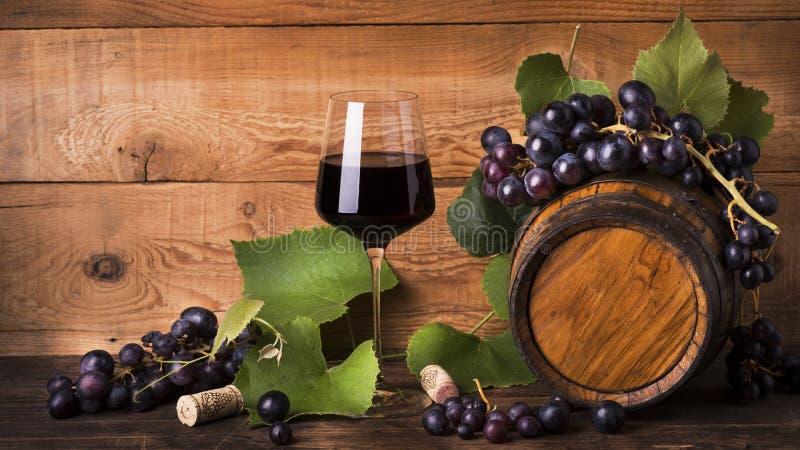 Todavía vida, cubilete de vino rojo, uvas y barril foto de archivo