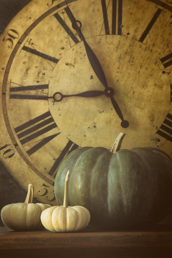 Todavía vida de calabazas y del reloj viejo fotos de archivo