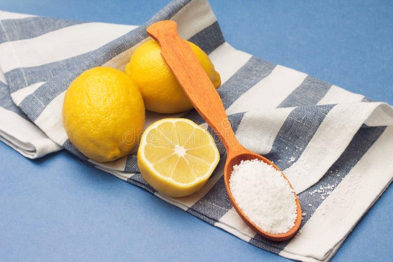 Todavía vida de limones, de la cuchara con el ácido cítrico y de la servilleta rayada fotografía de archivo