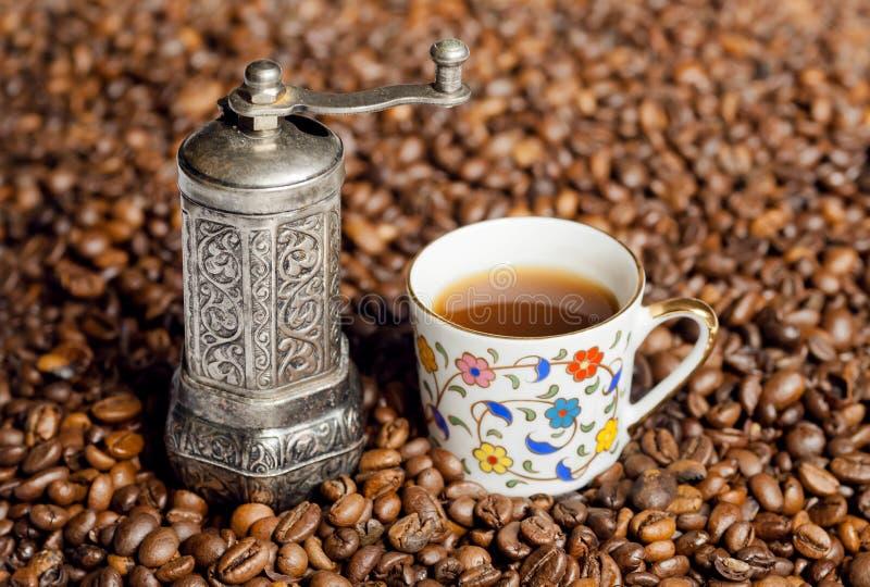 Todavía vida de los granos de café y de la amoladora de café con la taza oriental del estilo de café foto de archivo libre de regalías