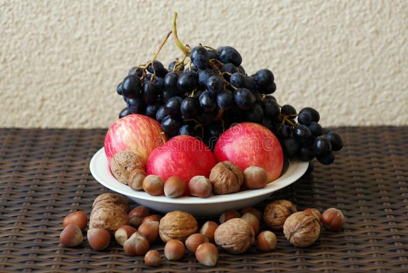 Todavía vida de manzanas rojas, de uvas azules y de nueces imagen de archivo libre de regalías