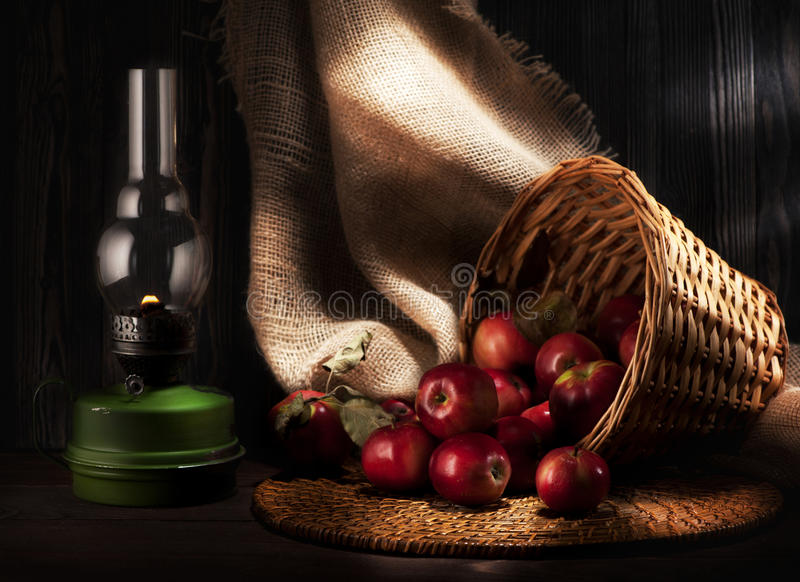 Todavía vida de manzanas y de la lámpara de keroseno Estilo rústico imagen de archivo