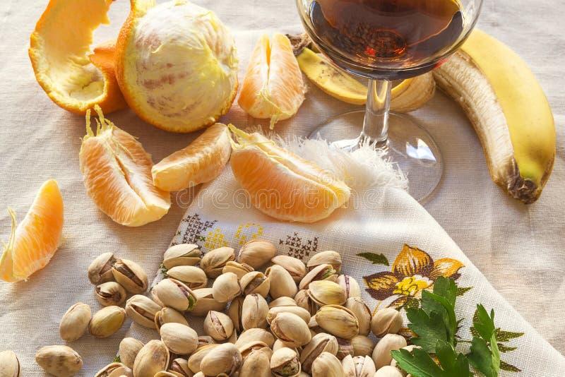Todavía vida de pistachos, peases de anaranjado y un vidrio de wiskey imágenes de archivo libres de regalías