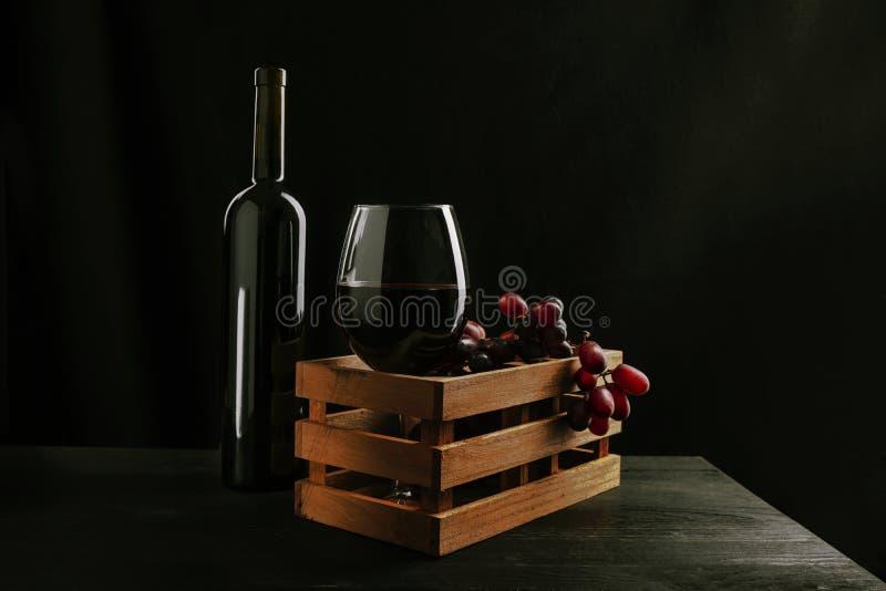 Todavía vida de una botella y de un vidrio de vino tinto dentro de una caja de madera con las uvas, fondo negro imágenes de archivo libres de regalías