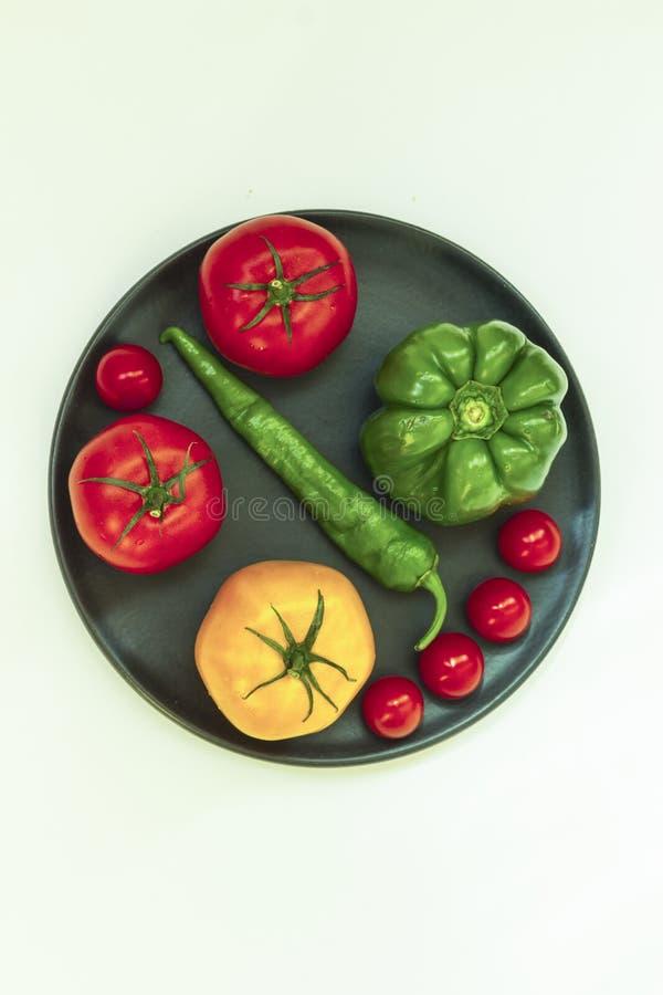 Todavía vida de verduras: tomates, pimientas y pepino en una placa negra Fondo blanco Visi?n superior fotografía de archivo
