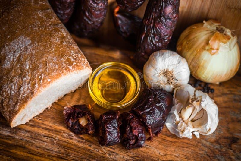 Todavía vida del bocado español mediterráneo de la cocina tradicional del pan del aceite de oliva de la cebolla del ajo de la sal fotografía de archivo libre de regalías