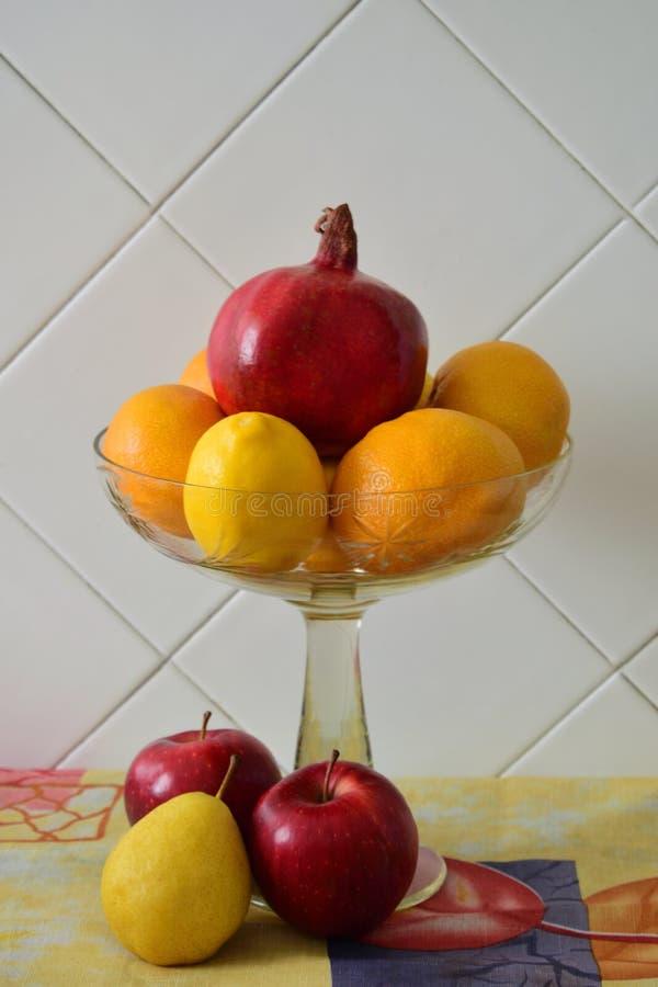 Todavía vida en un florero de cristal transparente con la granada, las mandarinas, el limón y la manzana rojos imagen de archivo