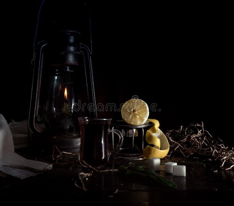 Todavía vida 1 Pequeño holandés lámpara de keroseno con el limón y el azúcar purificados en un fondo de madera de la oscuridad de imagenes de archivo