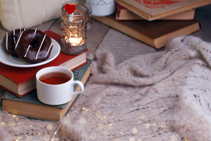 Todav?a detalles de la vida en el interior casero de la sala de estar Taza de anillos de espuma del té y del chocolate en la pila fotos de archivo