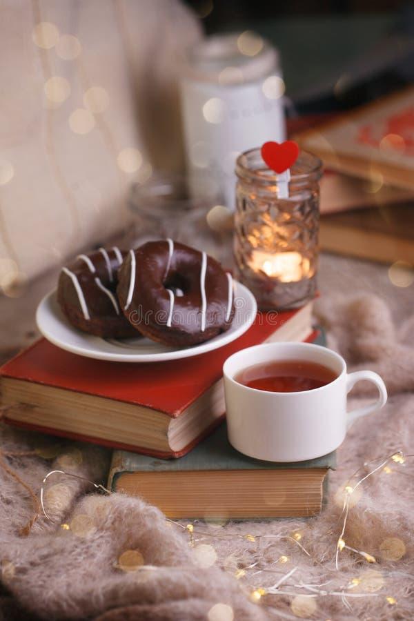 Todav?a detalles de la vida en el interior casero de la sala de estar Taza de anillos de espuma del té y del chocolate en la pila foto de archivo libre de regalías