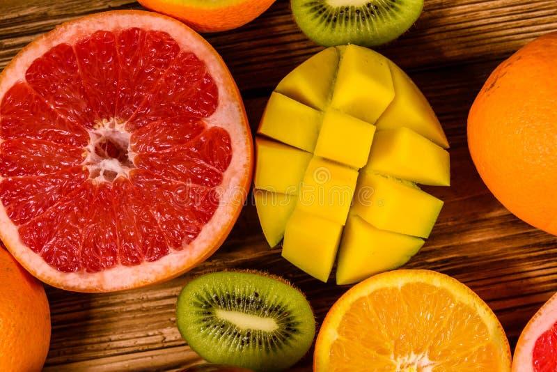 Todav?a vida con las frutas ex?ticas Mango, naranjas, pomelo y kiwis en la tabla de madera Visi?n superior imagen de archivo libre de regalías