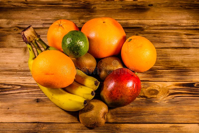 Todav?a vida con las frutas ex?ticas Pl?tanos, mango, naranjas, aguacate, pomelo y kiwis en la tabla de madera foto de archivo