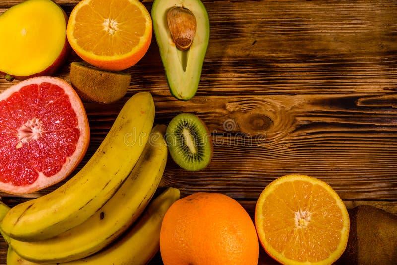 Todav?a vida con las frutas ex?ticas Pl?tanos, mango, naranjas, aguacate, pomelo y kiwis en la tabla de madera Visi?n superior imagenes de archivo