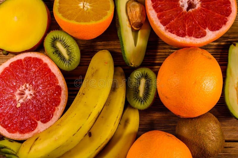 Todav?a vida con las frutas ex?ticas Pl?tanos, mango, naranjas, aguacate, pomelo y kiwis en la tabla de madera Visi?n superior foto de archivo libre de regalías