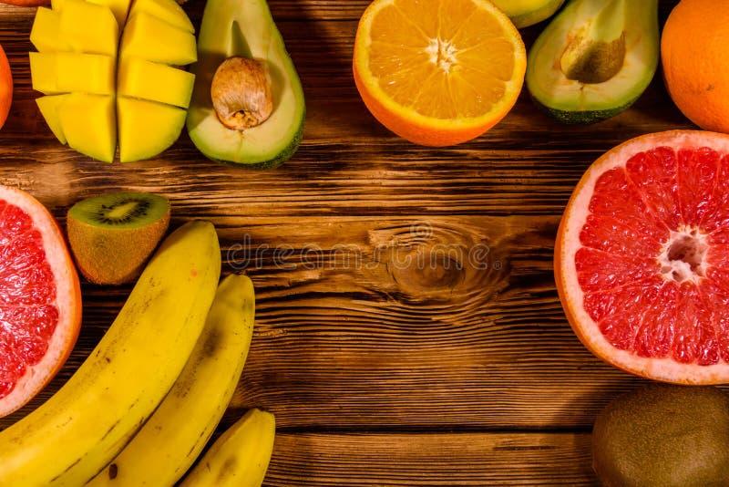 Todav?a vida con las frutas ex?ticas Pl?tanos, mango, naranjas, aguacate, pomelo y kiwis en la tabla de madera Visi?n superior fotos de archivo libres de regalías